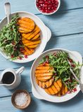 stock image of  grilled butternut squash, arugula and pomegranate salad on a blue wooden table, top view. clean, organic, seasonal, vegetarian foo