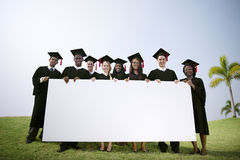 stock image of  group graduating students outdoors holding placard concept