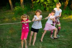 stock image of  group of happy children playing tug of war outside on grass. kids pulling rope at park