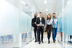 stock image of  group of happy young business people walking in office together