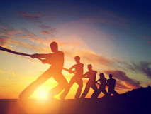 stock image of  group of people, team pulling line, playing tug of war.