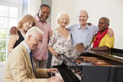 stock image of  group of seniors standing by piano and singing together