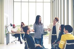 stock image of  group of young multiethnic creative team engaged brainstorm in small meeting while standing, sitting and talking together