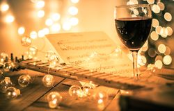 stock image of  guitar with instrumental sheet music and soft lights and red wine for christmas holiday, split tone