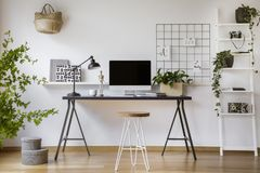 stock image of  hairpin stool standing by the wooden desk with mockup computer screen, metal lamp and coffee cup in real photo of white home offic
