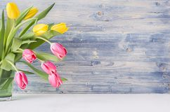 stock image of  half bouquet red and yellow tulips in green glass vase on blue shabby wooden background with copy space. spring easter home decor.