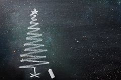 stock image of  hand drawn doodle christmas tree chalk blackboard in spiral form. sparkling glitter lights new year greeting card poster banner