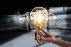 stock image of  hand holding light bulb and cog inside. idea and imagination.