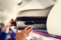 stock image of  hand-luggage compartment with suitcases in airplane. hands take off hand luggage. passenger put cabin bag cabin on the
