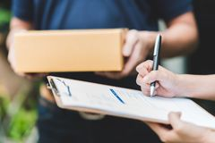 stock image of  hand putting signature in clipboard to receive package from delivery man
