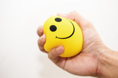 stock image of  hand squeeze yellow stress ball, on white background, anger management, positive thinking concepts