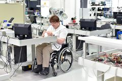 stock image of  handicapped worker in a wheelchair assembling electronic components in a modern factory at the workplace