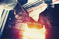 stock image of  handshaking business person in office. concept of teamwork and partnership. double exposure