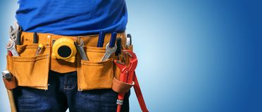 stock image of  handyman tool belt on blue background with copy space
