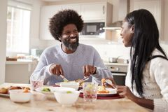 stock image of  happy black couple enjoying eating their sunday dinner together at home, close up