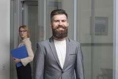 stock image of  happy businessman with blurred woman on background. bearded man in formal suit in office. confident man smile with beard
