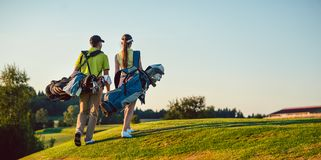 stock image of  happy couple wearing golf outfits while carrying stand bags
