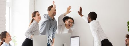 stock image of  happy diverse millennial workmates giving high five celebrating corporate success