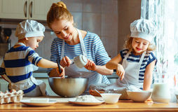 stock image of  happy family in kitchen. mother and children preparing dough, ba