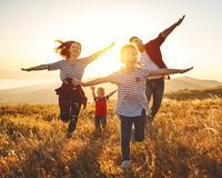stock image of  happy family: mother, father, children son and daughter on sunset