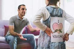 stock image of  happy father`s day concept. child daughter hiding postcard gift.
