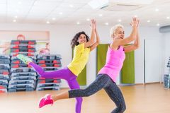 stock image of  happy female athletes doing aerobics exercises or zumba dance workout to lose weight during group classes in fitness