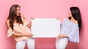 stock image of  happy girl friends holding blank advertisement board