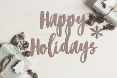 stock image of  happy holidays text, seasonal greetings card sign. flat lay. sty