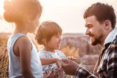 stock image of  dad playing with two little cute daughters