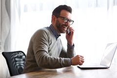 stock image of  happy man talking on cellphone in front of laptop computer