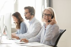 stock image of  happy mature female call center agent looking at camera smiling
