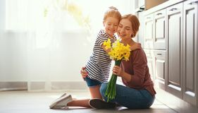 stock image of  happy mother`s day! child daughter   gives mother a bouquet of flowers to narcissus and gift