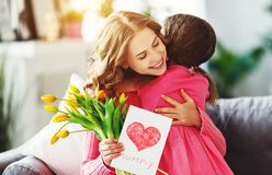 stock image of  happy mother`s day! child daughter gives mother a bouquet of flowers to tulips and postcard