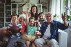 stock image of  happy multi-generation family watching soccer match on television in living room