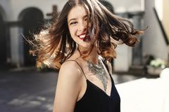 stock image of  happy stylish woman waving hair in sunlight at old european city