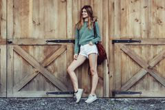 stock image of  happy woman with long legs look to the side near barn on the farm wearing casual outfit with shorts, backpack and sneakers.