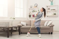 stock image of  woman in uniform cleaning home with mop and having fun