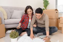 stock image of  happy young couple looking at blueprint planning new home interior design settling in, homeowners talking about remodeling