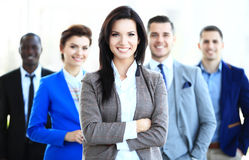 stock image of  happy young female business leader standing in front of her team