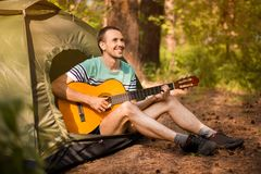 stock image of  happy young man camping and strum a guitar instrumental music to relax against background of forest sunset.