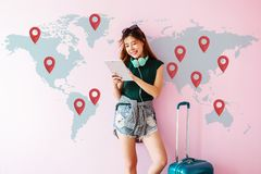 stock image of  happy young traveler woman standing with suitcase and using tablet to finding her destination for next trip. technology on travel