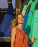 stock image of  head and shoulders portrait of young beautiful and happy blond woman smiling relaxed and cheerful posing with colorful surf boards
