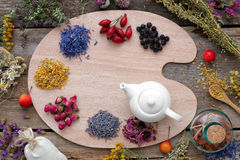 stock image of  healing herbs on wooden palette and tea kettle, top view.