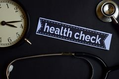 stock image of  health check on the print paper with healthcare concept inspiration. alarm clock, black stethoscope.