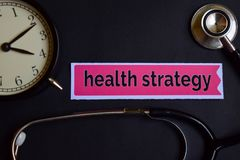 stock image of  health strategy on the print paper with healthcare concept inspiration. alarm clock, black stethoscope.
