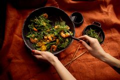 stock image of  healthy diet. salad of arugula, tiger prawns and oranges. light dish with seafood.diet menu. hands interfere salad