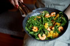 stock image of  healthy diet. salad of arugula, tiger prawns and oranges. light dish with seafood. diet menu.hands interfere salad