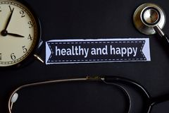 stock image of  healthy and happy on the print paper with healthcare concept inspiration. alarm clock, black stethoscope.