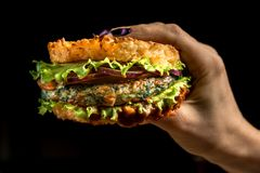 stock image of  healthy lifestyle, proper nutrition. healthy rice burger with vegetables, herbs and cutlet in female hands