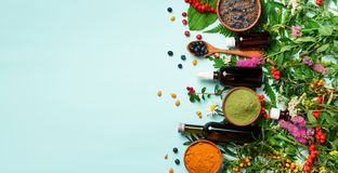 stock image of  healthy super food, berries, turmeric, spirulina, omega acid capsules, vitamin c supplement, medicinal herbs and spices on blue